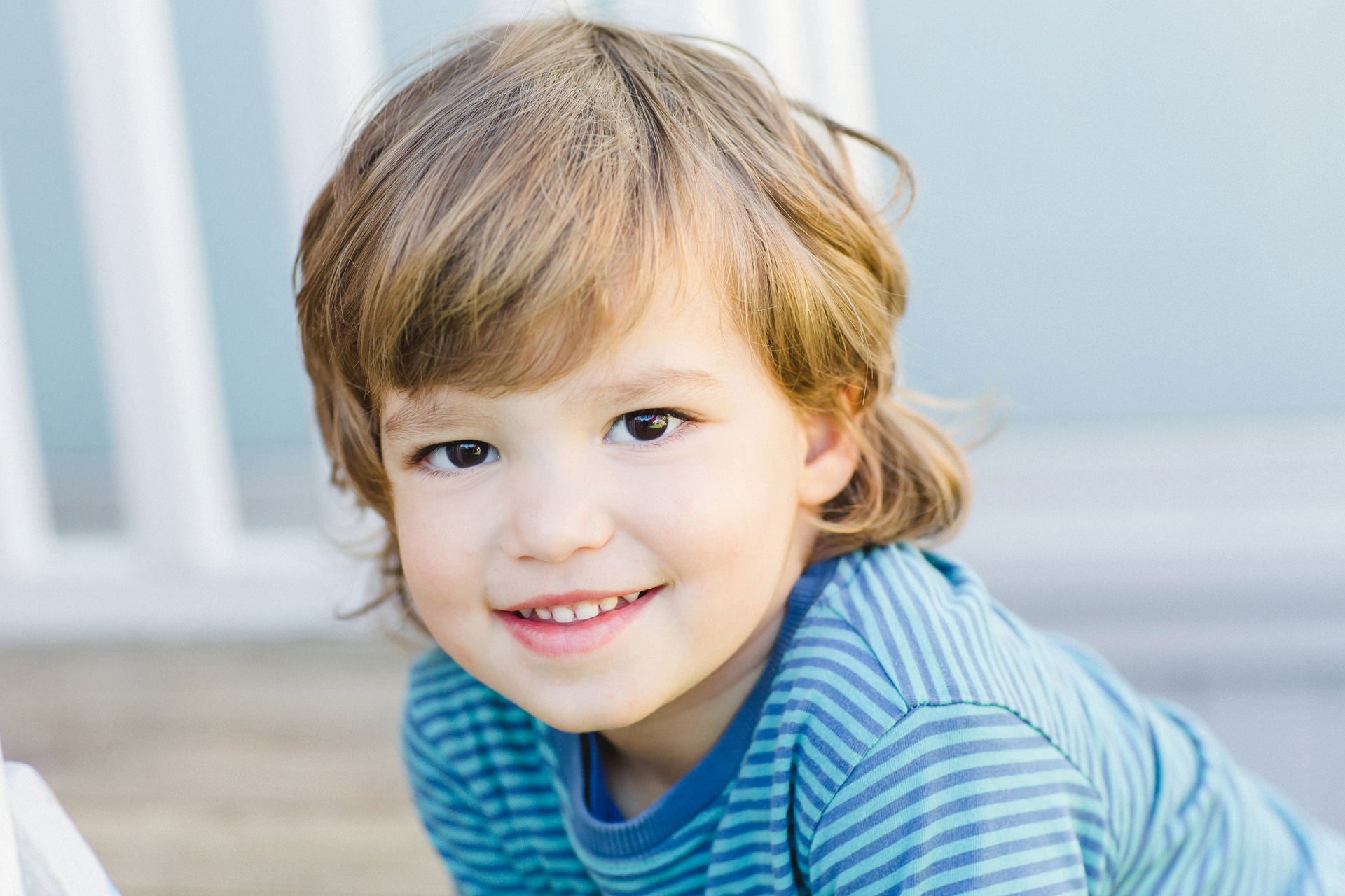 a little boy with brown eyes wearing a blue striped top and smiling at the camera